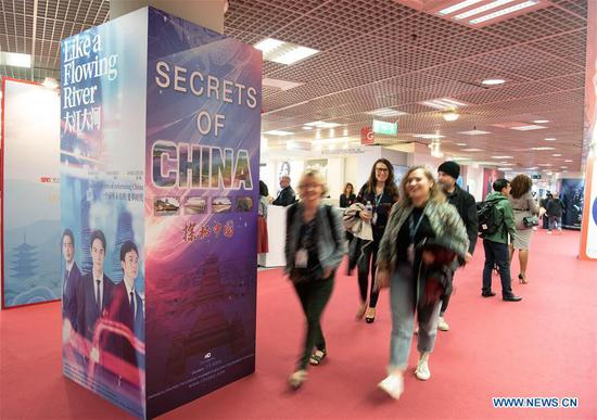 People walk past a poster of Chinese TV series during the 2019 Cannes International Series Festival, or Canneseries 2019, in Cannes, France, April 8, 2019. Many TV series, documents and cartoons presented by Chinese exhibitors drew people's attention during the big event running from 5 to 10 April. (Xinhua/Jack Chan)