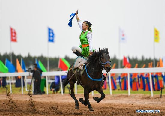 A woman performs horse riding at the Genghis Khan Chagan Suluk Nadam Fair in Ejin Horo Banner of Ordos City, north China's Inner Mongolia Autonomous Region, April 24, 2019. The two-day fair kicked off on Wednesday, including a variety of traditional activities. (Xinhua/Peng Yuan)