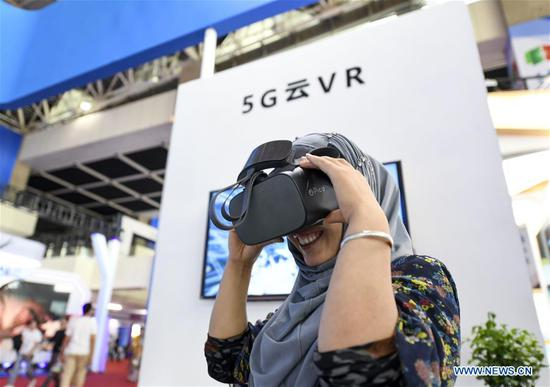A visitor tries on a 5G cloud-based virtual reality (VR) device at an exhibition of high technologies and equipment during the fourth China-Arab States Expo in Yinchuan, northwest China's Ningxia Hui Autonomous Region, Sept. 6, 2019. The fourth China-Arab States Expo has helped promote cross-border high-tech exchange and cooperation. At an exhibition of high technologies and equipment held as part of the expo, visitors are exposed to major scientific and technological breakthroughs and state-of-the-art equipment developed by the high-tech sector. (Xinhua/Feng Kaihua)