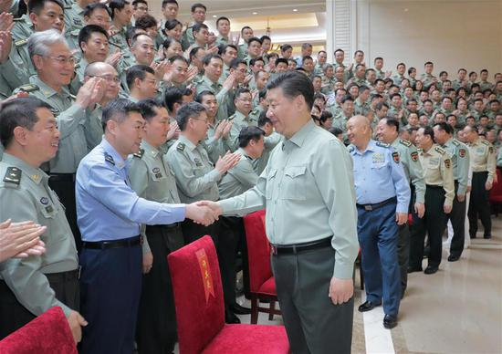 Chinese President Xi Jinping, also general secretary of the Communist Party of China (CPC) Central Committee and chairman of the Central Military Commission, shakes hands with delegates of the 8th CPC Congress of the People's Liberation Army Academy of Military Science during an inspection of the academy on May 16, 2018. (Xinhua/Li Gang)