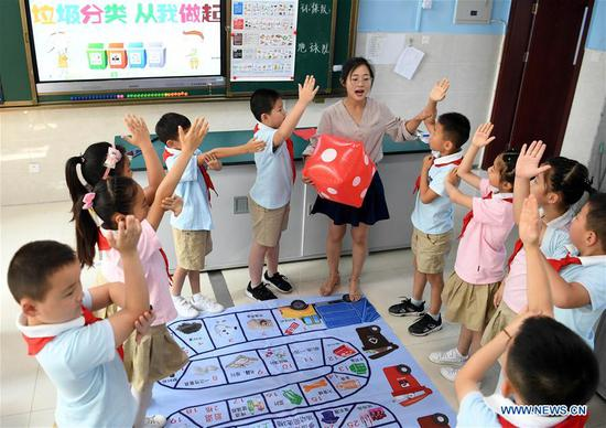 Pupils take part in a garbage classification game under the guidance of a teacher at Jianping Experimental Primary School in Hefei, capital of east China's Anhui Province, July 11, 2019. The primary school held activities to teach children garbage classification knowledge on Thursday. (Xinhua/Liu Junxi)