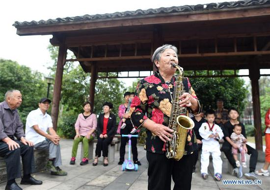 Ying Miaofang plays the saxophone at a park in Yingdianjie Township of Zhuji City, east China's Zhejiang Province, Oct. 6, 2019. Ying Miaofang, 80, is widely known for her warm-heartedness. An illustration is the assistance Ying provided for college students to help them finish undergraduate study, with about 60,000 yuan (about 8,394.31 U.S. dollars) she donated for three consecutive years. In addition, Ying has devoted herself to honing peony painting techniques on moon-shaped fans since 2013 and plans to donate 2,000 fans she will finish next year for public welfare. (Xinhua/Han Chuanhao)