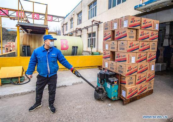 A worker transports disinfectants at a workshop in Yuncheng City, north China's Shanxi Province, Jan. 27, 2020. To help fight the outbreak of pneumonia caused by novel coronavirus, workers in factories in Shanxi work overtime to meet with the increasing need. (Photo by Xue Jun/Xinhua)