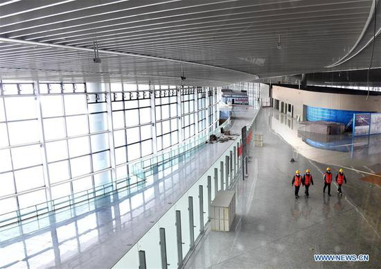 Staff members walk through the departure hall of the terminal building of Jiaodong International Airport in Qingdao, east China's Shandong Province, March 25, 2020. The construction work of the airport was fully resumed recently. (Xinhua/Li Ziheng)