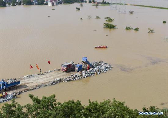 Aerial photo taken on July 12, 2020 shows the construction site of a breached dyke in Poyang Town of Poyang County, east China's Jiangxi Province. The embankment of a river in east China's Jiangxi Province was breached late Wednesday following continuous torrential rains, forcing over 9,000 residents to evacuate. (Xinhua/Zhou Mi)