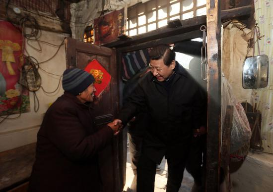 In this file photo taken on Dec. 30, 2012, Xi Jinping (R) visits an impoverished villager in the Luotuowan Village of Fuping County, north China's Hebei Province. (Xinhua/Lan Hongguang)