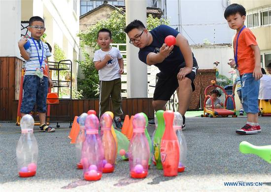 Guo Xinwang plays games with children at the Xiaoxihu kindergarten in Nanjing, capital of east China's Jiangsu Province, Sept. 6, 2018. Guo, born in 1993 and graduated from the Jiangsu Normal University, became the first and only male teacher of the Xiaoxihu kindergarten three years ago. There are 400 plus male teachers in Nanjing nowadays, up to three percent of the whole teachers working in kindergartens. (Xinhua/Li Bo)