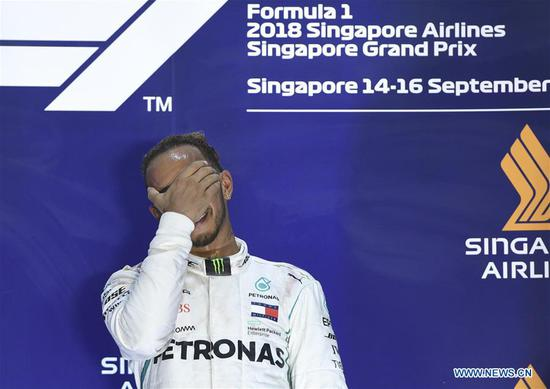 First-placed Mercedes' driver Lewis Hamilton (C) of Britain celebrates during the awarding ceremony of the 2018 Singapore Formula One Grand Prix held at the Marina Bay Street Circuit in Singapore, on Sept. 16, 2018. (Xinhua/Then Chih Wey)