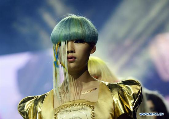 A model presents hair styling during a fashion show in Hangzhou, capital of east China's Zhejiang Province, July 4, 2014. Along with China's reform and opening-up starting from 1978, Chinese women have refreshed their images year after year, which can be simply seen from their hairstyles. Women's hairstyles, just like a mirror, reflect fashion changes and most importantly, Chinese women's increasingly diversified definition of beauty. (Xinhua/Li Zhong)