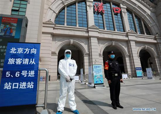 Police officers stand guard at Hankou Railway Station in Wuhan, central China's Hubei Province, April 6, 2020. The central Chinese city of Wuhan, once the epicenter of the novel coronavirus outbreak, will resume operation of nearly 100 passenger trains starting April 8, according to the local railway operator. Trains have started arriving in 17 stations in Wuhan since March 28, and outbound trains will start to resume services on April 8, according to local authorities. (Photo by Zhao Jun/Xinhua)