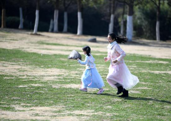Children play at Feicui Lake park in Hefei, east China's Anhui Province, Feb. 13, 2021, the second day of the Chinese Lunar New Year. (Xinhua/Liu Junxi)