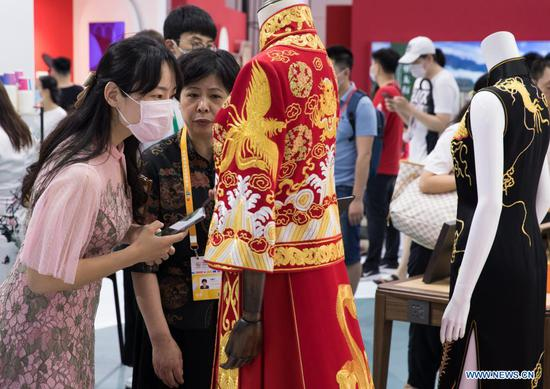 A visitor views a Qipao (cheongsam) on display in the Provinces, Municipalities, Autonomous Regions of China Exhibition Hall during the first China International Consumer Products Expo in Haikou, capital of south China's Hainan Province, May 9, 2021. (Xinhua/Jin Liwang)