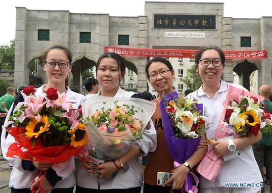 Students pose for a group photo with their teacher after the exam in Beijing, capital of China, June 8, 2018. The national college entrance examination ended in some places of China on Friday. (Xinhua/Luo Xiaoguang)