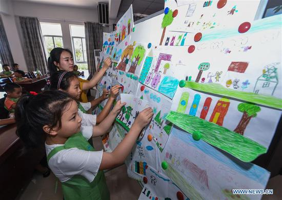 Students put on their paintings about their hometown during a class at a school in Lincheng Township in Changxing County, east China's Zhejiang Province, July 10, 2018. Volunteers from Hangzhou Normal University and government officials organized the class to teach students how to classify the garbage and reuse the waste. (Xinhua/Xu Yu)