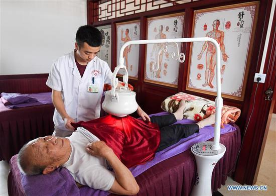 An old man receives physiotherapy at an elder care center in Fenglin Village of Xingguo County, east China's Jiangxi Province, Aug. 19, 2019. Rural revitalization strategy was first put forward during the 19th National Congress of the Communist Party of China in 2017 and repeatedly stressed by the Chinese leadership since then. The strategy's overall goal is to build rural areas with thriving businesses, pleasant living environments, social etiquette and civility, effective governance, and prosperity. (Xinhua/Chen Yehua)