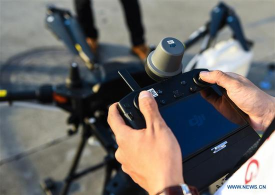 A man tries the remote controller of Chinese drone maker DJI's latest crop protection drone, the T20, at a product launch event in Shenzhen, south China's Guangdong Province, Nov. 5, 2019. Besides the new T20 crop protection drone, DJI also introduced an upgraded version of the drone's spray system as well as appertaining service and training plans on Tuesday. (Xinhua/Mao Siqian)