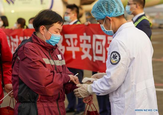 A medical worker returned from virus-hit Hubei Province receives temperature checking at Chongqing Jiangbei International Airport in southwest China's Chongqing, March 18, 2020. Medical assistance teams started leaving Hubei Province as the epidemic outbreak in the hard-hit province has been subdued. (Xinhua/Liu Chan)