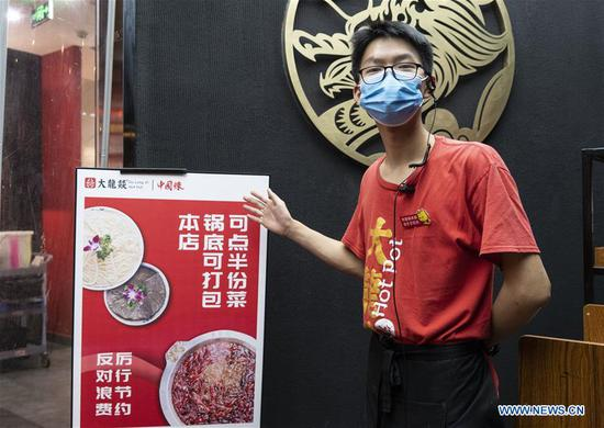 A staff member explains the measures to reduce food waste at a hot-pot restaurant in Chengdu, southwest China's Sichuan Province, Sept. 7, 2020. Many hot-pot restaurants in Chengdu have introduced measures such as offering smaller portions of food and takeaway services in their campaigns against food waste. (Xinhua/Li Mengxin)