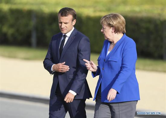 French President Emmanuel Macron (L) and German Chancellor Angela Merkel talk prior to the family photo session during the North Atlantic Treaty Organization (NATO) summit in Brussels, Belgium, on July 11, 2018. The North Atlantic Treaty Organization (NATO) summit began Wednesday in Brussels with verbal fireworks as recent tensions between allies and the United States were laid bare by U.S. President Donald Trump in a growing row over burden sharing and foreign influence. (Xinhua/Ye Pingfan)