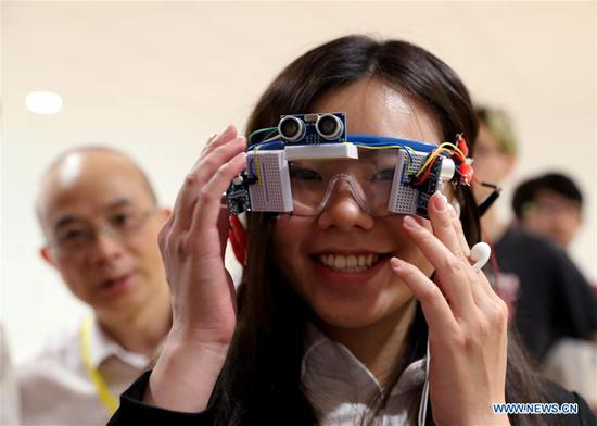 A college student shows a glasses control system that can guide for the blind during a design show in Shanghai, east China, Aug. 8, 2018. A summer design show was held in Shanghai Jiao Tong University on Wednesday, during which more than 80 creative designs, mainly on artificial intelligence and internet, were displayed. (Xinhua/Liu Ying)