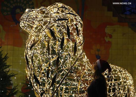 A zoo staff poses with a lion-shaped light installation during the launch of