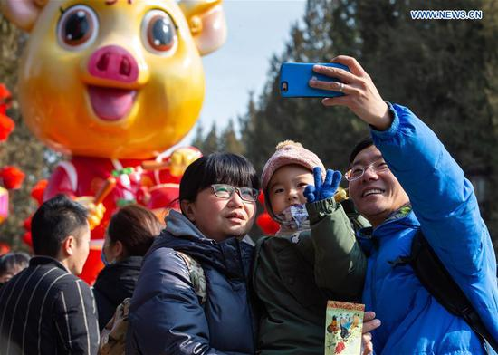 Visitors take selfies at a temple fair at Ditan Park in Beijing, capital of China, Feb. 8, 2019. (Xinhua/Su Yang)