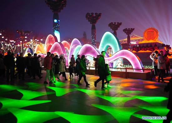 Tourists visit the decorated Kaiyuan Square in Xi'an, capital of northwest China's Shaanxi Province, Feb. 5, 2019. The city is in festive mood with its colourful lights at night during the Spring Festival. (Xinhua/Shao Rui)