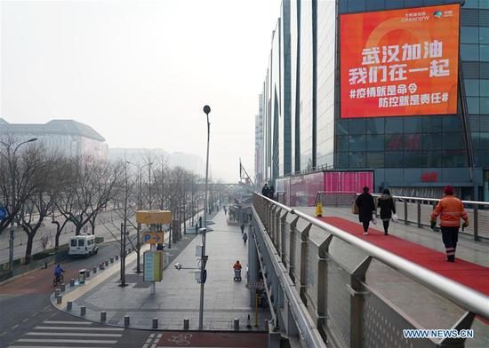 A placard showing support to Wuhan is seen on a building in the Xidan business area in Beijing, capital of China, on Feb. 12, 2020. Work and production has resumed gradually in enterprises, communities and malls, etc. in Beijing since Feb. 10 with comprehensive measures taken to prevent and control the epidemic caused by the novel coronavirus. (Xinhua/Zhang Chenlin)