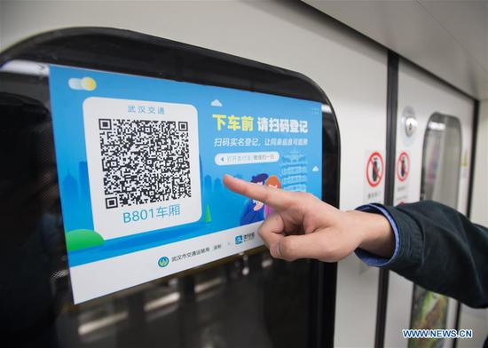 A staff displays the QR code for real-name registration on a subway carriage at a train depot in Wuhan, central China's Hubei Province, March 23, 2020. Wuhan is making preparations for restoring the operation of public transportation. The public need to go through real-name registration for taking public transportation or taxis in Wuhan, capital of central China's Hubei Province, authorities said Sunday. (Xinhua/Xiao Yijiu)
