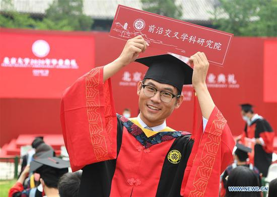 A graduate poses for a photo before the commencement ceremony of Peking University in Beijing, capital of China, July 2, 2020. Peking University held its commencement ceremony in Beijing on Thursday. Due to COVID-19 prevention and control measures, a limited number of graduates attended the ceremony at nine venues on site while others participated online. (Xinhua/Ren Chao)
