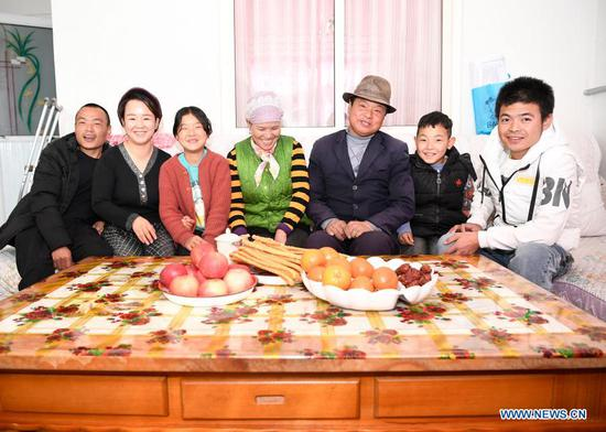 Zhang Junming (3rd R) poses for a family portrait one day before the Chinese Lunar New Year at his new residence at the Binhe Jiayuan relocation site in Yinchuan, northwest China's Ningxia Hui Autonomous Region, Feb. 11, 2021. Zhang Junming, 55, once lived in Hongbaiyang Township, an economic backwater in southern Ningxia. When he was young, Zhang had been severely injured in an accident, and hence suffered from leg disabilities that prevented him from seeking job opportunities in the big cities. So he and his family had to scrape a living out of poor yields on the barren farmland. The quality of life was exacerbated by lack of drinking water and poor traffic condition. Such difficult scenario came to a turning point in 2013, when the Zhang family moved out of Hongbaiyang under a government-backed ecological poverty-relief relocation scheme. The relocation site they moved into has paved roads, sound infrastructure and a slew of support policies, which rekindled Zhang's hope for the future. Eight years since the relocation, huge changes have taken place in the life of the Zhang family. At present, Zhang's two sons work in the regional capital Yinchuan, whereas his daughter-in-law is employed in a textile factory nearby. Meanwhile, both Zhang and his wife earn from job posts with social sponsorship. (Xinhua/Wang Peng)