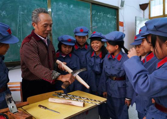 Xiao Qinghua presents the making skills of suona horn to students at the Changzhengyuan primary school in Yudu County, east China's Jiangxi Province, on Oct. 11, 2018. Xiao, an inheritor of the national intangible cultural heritage