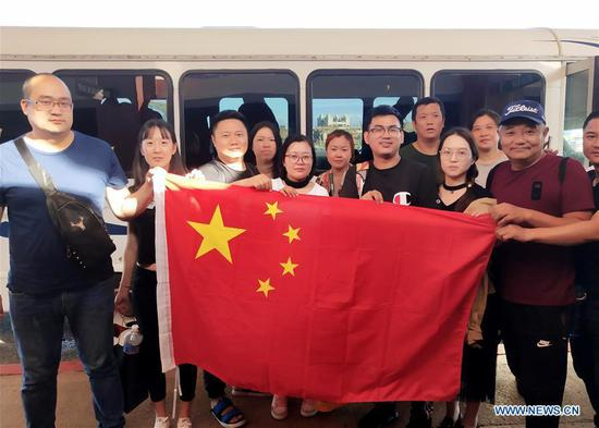 Chinese tourists pose with Chinese national flag before starting to fly back home in Saipan, the Commonwealth of the Northern Mariana Islands (CNMI), Oct. 28, 2018. Some 1,500 Chinese tourists trapped in Saipan by Super Typhoon Yutu started to fly back home on Sunday. (Xinhua)