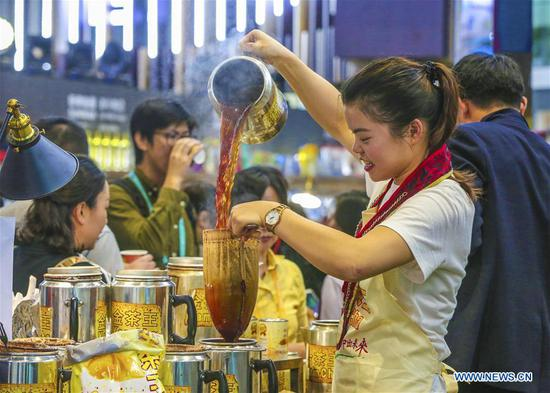 A staff member makes milk tea at the Food & Agricultural Products area during the first China International Import Expo (CIIE) in Shanghai, east China, Nov. 7, 2018. Various food from all over the world are exhibited in the CIIE. (Xinhua/Yin Gang)