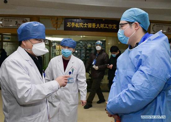 A doctor speaks with a cured novel coronavirus pneumonia patient in Wuhan, central China's Hubei Province, Feb. 6, 2020. A total of 23 novel coronavirus pneumonia patients were cured and discharged from hospital on Thursday after integrated treatment with traditional Chinese medicine (TCM) and Western medicine. (Xinhua/Li He)