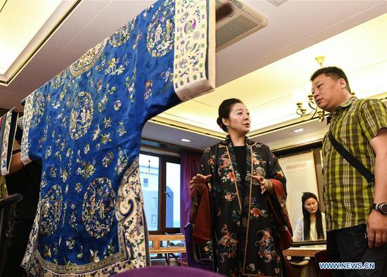 Collector and costume designer Bi Hong (L) introduces a traditional Chinese embroidery costume to a visitor during an exhibition of traditional costumes and embroidery artworks in Beijing, capital of China, June 3, 2018. (Xinhua/Li He)