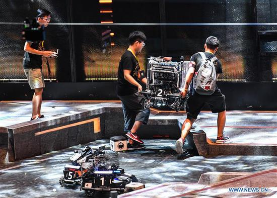 Participants test robots during the finals of the 18th RoboMaster Robotics Competition in Shenzhen, south China's Guangdong Province, Aug. 6, 2019. The final tournament of the 18th RoboMaster Robotics Competition kicked off here on Tuesday, with 32 teams from home and abroad competing for the championship. (Xinhua/Jin Yu)