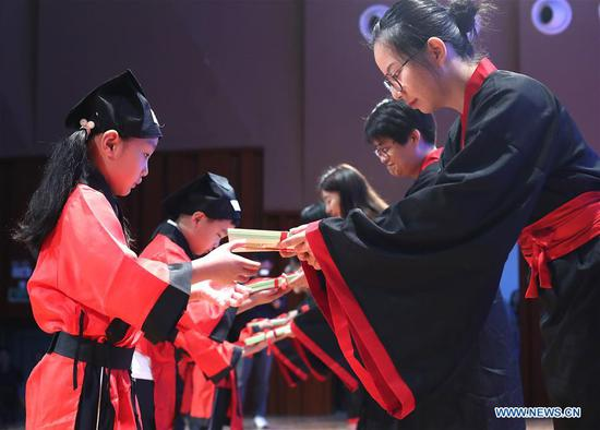Students in traditional costumes attend an event marking the symbolic first class of the new semester at a primary school in Shanghai, east China, Sept. 2, 2019. (Xinhua/Chen Fei)