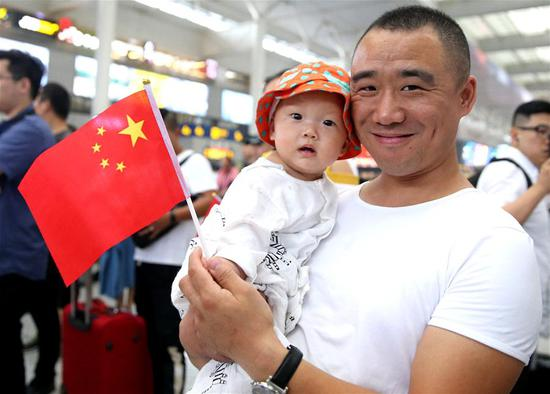 A man takes part in a flash mob with a child at Shanghai Hongqiao Railway Station in east China's Shanghai, Sept. 17, 2019. Participants chorused patriotic songs during the flash mob as a way to celebrate the 70th anniversary of the founding of the People's Republic of China. (Xinhua/Chen Fei)
