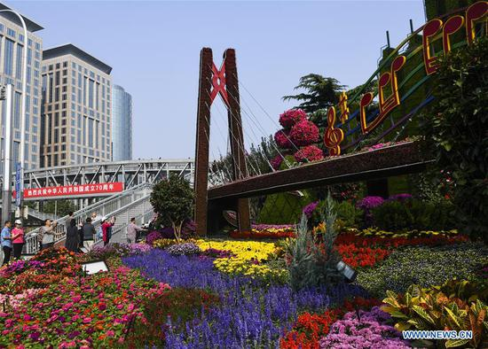 People visit a flowerbed titled