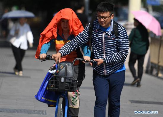 A pedestrian (L) puts a jacket over her head and shoulders as sun shade in Beijing, capital of China, May 22, 2019. Beijing's observatory issued a yellow alert on Tuesday for high temperatures over the next four days. Temperature could rise to 35 degrees Celsius from Wednesday to Saturday, and reach up to 37 degrees Celsius on Thursday. (Xinhua/Zhang Chenlin)