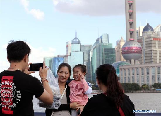 Tourists pose for photos at the Bund in east China's Shanghai, Oct. 8, 2020. (Xinhua/Liu Ying)