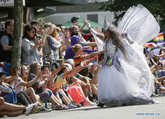A reveller interacts with the crowds on the street during the 40th Vancouver Pride Parade in Vancouver, Canada, Aug. 5, 2018. (Xinhua/Liang Sen)