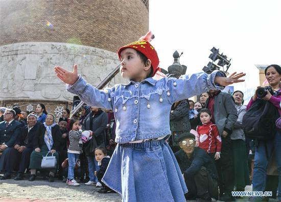 A child dances at the square of the Xinjiang International Grand Bazaar in Urumqi, capital of northwest China's Xinjiang Uygur Autonomous Region, April 4, 2019. The market, which has witnessed a booming tourism, received about 1.33 million visits in March alone. (Xinhua/Wang Fei)