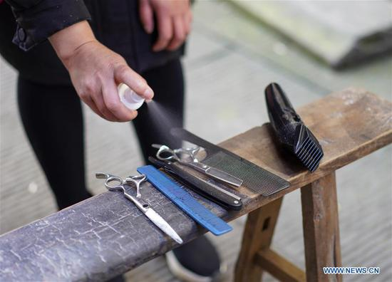 A volunteer barber disinfects tools at a community in southwest China's Chongqing Municipality, Feb. 16, 2020. Since the outbreak of the novel coronavirus, most barbershops have been closed. A community in Beibei District of Chongqing organized a team of volunteer barbers to provide free haircuts for its residents. (Xinhua/Liu Chan)