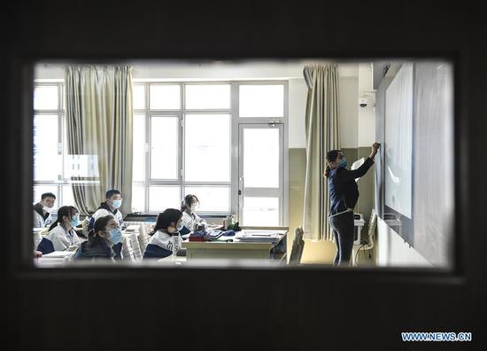 Students have an English class at Urumqi No.1 Senior High School in Urumqi, northwest China's Xinjiang Uygur Autonomous Region, March 19, 2020. As of Friday, over 10 provinces and regions across the country have announced dates and arrangements for starting the new semester, most of which put graduating middle and high school students at priority. Among them, Qinghai, Guizhou and Xinjiang have already resumed classes for some students, while the rest have scheduled reopening schools in late March or early April. (Xinhua/Wang Fei)