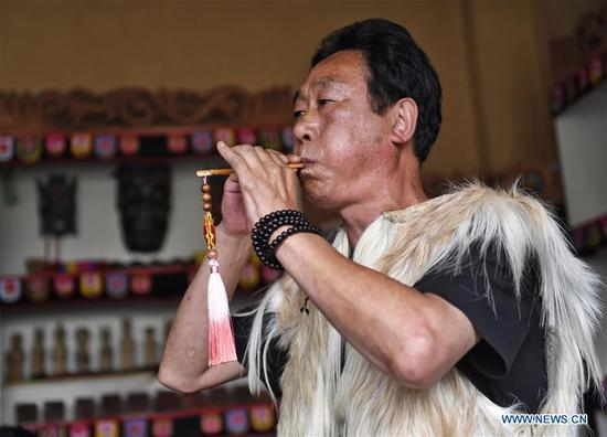 Artist He Wangjin plays flute of Qiang ethnic group at a workshop about intangible cultural heritage in Maoxian County of Aba Tibetan and Qiang Autonomous Prefecture, southwest China's Sichuan Province, June 22, 2020. Located in northwest of Sichuan Province, with nearly one million population, Aba Tibetan and Qiang Autonomous Prefecture has a diversity of ethnic minority groups, including Tibetan, Qiang and Hui, etc. In recent years, to better inherit the ethnic culture, local schools have introduced more traditional cultural courses while local authorities set up training workshops about intangible cultural heritage to help local villagers learn traditional crafts, as a way to boost their incomes. In 2018, the production value of cultural industry in this prefecture has reached about 1.2 billion yuan (about 169.8 million U.S. dollars), accounting for 3.32 percent of gross domestic product (GDP) of this prefecture. (Xinhua/Liu Kun)