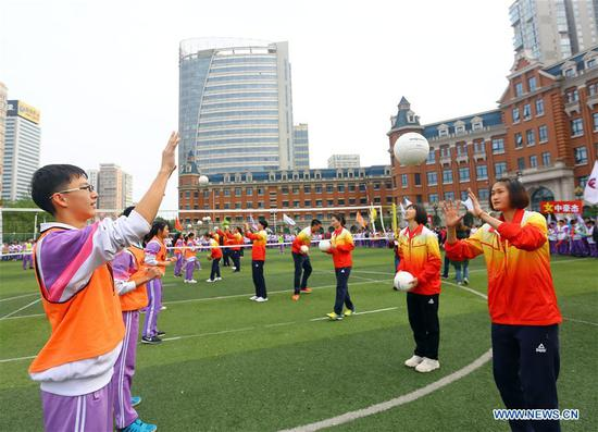 Students of Tianjin No. 11 Middle School practice with the members of Tianjin women's volleyball team at the playground in the school in Tianjin, north China, April 23, 2018. Tianjin women's volleyball team has claimed their 11th Chinese Women's Volleyball Super League title this year. (Xinhua/Liu Dongyue)