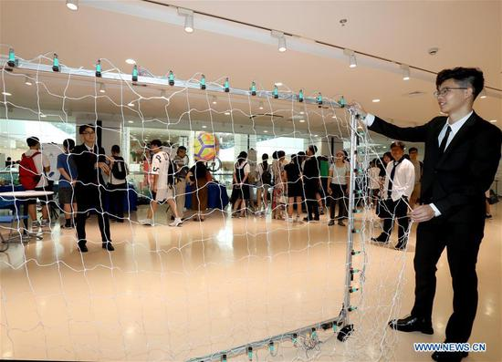 A college student shows a penalty training system based on light and electricity sensor location during a design show in Shanghai, east China, Aug. 8, 2018. A summer design show was held in Shanghai Jiao Tong University on Wednesday, during which more than 80 creative designs, mainly on artificial intelligence and internet, were displayed. (Xinhua/Liu Ying)