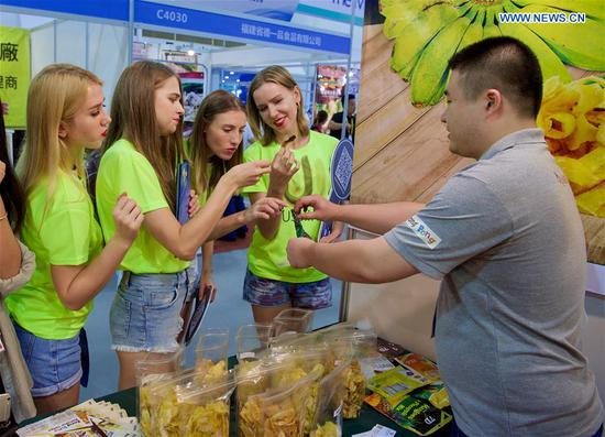 Visitors from Ukraine taste food at the 20th China International Fair for Investment and Trade in Xiamen, southeast China's Fujian Province, Sept. 8, 2018. (Xinhua/Jiang Kehong)